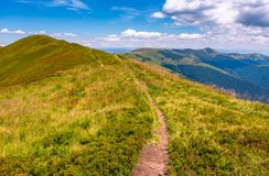 Path on top of Carpathian mountain ridge. Beautiful summer landscape under gorgeous sky with clouds Royalty Free Stock Photo