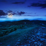 Path on top of mountain meadow at night. Summer landscape. path  on top of the meadow on the hillside. forest in fog on the mountain at night in  full moon light Royalty Free Stock Image