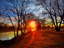 Path Towards The Light. Walking path towards the brught sunset light shining brightly through the trees by the Raritan River in a park in New Jersey stock images