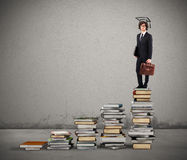 Path of undergraduate studies. Scale with books and man with graduation hat Royalty Free Stock Photos
