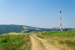 Hill path. A path up on the hills of Transylvania in summer time. A GSM antenna is also captured in the picture Royalty Free Stock Photo