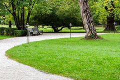 A path of white gravel in the park. The path of white gravel in the park along the gravel path, garden shrubs, white trees Royalty Free Stock Photos
