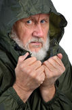 Pathetic senior man. In green waterproof jacket, may be homeless and jobless Royalty Free Stock Photo