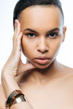 Pathetic young Negroid woman posing in the studio. Graceful model. Elegant pathetic young Negroid woman touching her face while standing isolated in white Stock Image