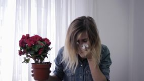 Pathogen, young girl with flower in hands suffers from an allergy to pollen constantly sneezes and wipes with stock video footage