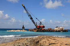 Crane on barge stacks stones in the sea to protect the shore fro. PATHOS, CYPROS - JANUARY 12, 2018: Crane on barge stacks stones in the sea to protect the shore royalty free stock photo