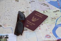 Thailand passport and sunglasses on the map, Prepare to travel. Pathumthani, Thailand - June 8, 2017 : Thailand passport and sunglasses on the map, Prepare to royalty free stock image