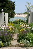 The Pathway. An open gate and stepping stones thru the flowers to the ocean Stock Photography