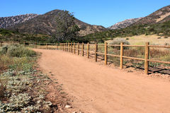 Pathway across the hills, dry grass fields. Pathway with wooden fence, next to rocky hills and adjoining dry grass fields, meadows Royalty Free Stock Images