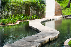 A pathway across a man made pond Stock Image