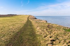 Reculver, Kent, UK along the cliff top walk on the coast near to. Pathway along the grass covered coastal clifftops of Reuclver country park near to Reculver Stock Image