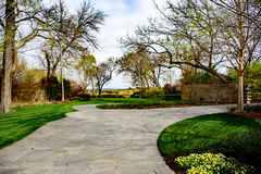 Pathway along manicured lawn with flowers and trees Stock Images