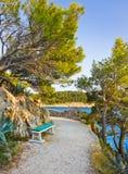 Pathway, bench and sea at Makarska, Croatia Royalty Free Stock Photos