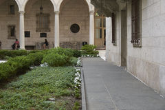 Pathway in Boston Library. Tiles pathway through the gardens in the courtyard of the Boston Library. Archways frame background Royalty Free Stock Photo