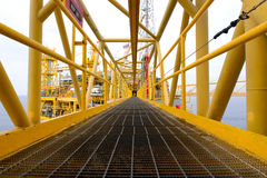 The pathway bridge of offshore oil rig. The worker is walking cross the pathway bridge of offshore oil rig Royalty Free Stock Photos