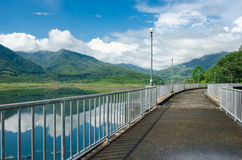 Pathway on the dam for looking view mountain and water in dam Stock Image