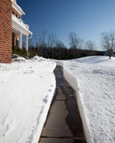 Pathway dug to modern brick house. Pathway cut through deep snow towards the door of a modern single family home stock image