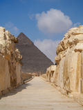 Pathway through Egyptian Ruins with Pyramid in Background Stock Photography