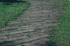 Pathway in garden,green lawns with Wooden floor pathways Royalty Free Stock Photo