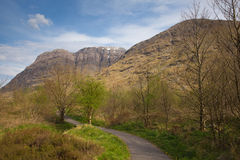 Pathway in Glencoe valley with snow topped mountains Scotland UK in Scottish Highlands Stock Image
