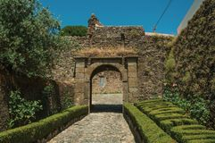 Pathway going toward gateway in stone wall with garden stock photography