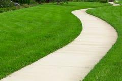 Pathway through green lawn Stock Photo