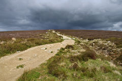 Pathway illuminated by the sun with storm clouds in background. Walking the wicklow way passing fairy castle i didn't went up their because of the clouds stock photography