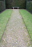 Pathway leading to a garden bench Royalty Free Stock Photo