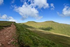 Pathway leading up to the summit of Pen y Fan in the Brecon Beacons National Park. The view along the trail leading down from the peak of Cribyn up to the summit Royalty Free Stock Image