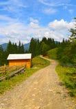 Pathway in mountains nearVorokhta, Ukraine. Pathway and wooden lodge in mountains at sunny summer day, Vorokhta region, Ukraine Royalty Free Stock Photos