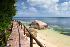 Pathway by the ocean with big stones and green plants Stock Photography