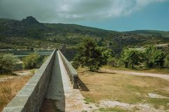 Pathway over the concrete dam of Rossim Lake. On a hilly landscape, in a cloudy day at the highlands of Serra da Estrela. The highest mountain range in stock photo