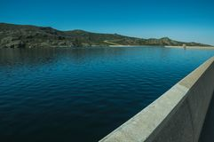 Pathway over dam wall forming a lake on highlands. Parapet on the Marques da Silva concrete dam forming the Long Lake on highlands, in a sunny day at the Serra royalty free stock photography