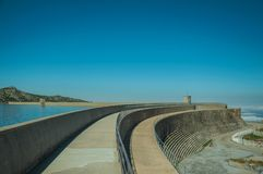 Pathway over dam wall forming a lake on highlands. Pathway over the Marques da Silva concrete dam forming the Long Lake on highlands, in a sunny day at the Serra royalty free stock photo
