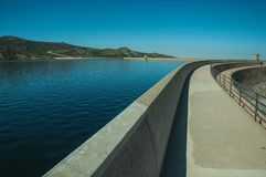 Pathway over dam wall forming a lake on highlands. Pathway over the Marques da Silva concrete dam forming the Long Lake on highlands, in a sunny day at the Serra stock images