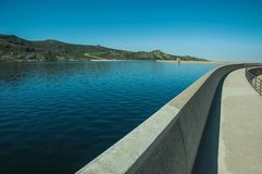 Pathway over dam wall forming a lake on highlands. Pathway over the Marques da Silva concrete dam forming the Long Lake on highlands, in a sunny day at the Serra royalty free stock image