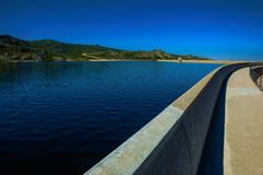 Pathway over dam wall forming a lake on highlands. Pathway over the Marques da Silva dam forming the Long Lake on highlands, at the Serra da Estrela. The highest stock photography