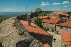Pathway over stone wall next to old houses roofs. Pathway over thick stone wall next to old houses roofs and verdant hilly landscape, in a sunny day at Sortelha stock image