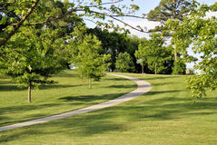 Pathway through park. Scenic view of pathway receding through green grass and trees in picturesque park Royalty Free Stock Photo