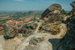 Pathway passing through big rocks in Monsanto. Pathway passing through big round rocks and the Monsanto village underneath the hilly landscape. This township is royalty free stock photography