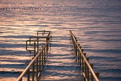 A pathway at sunset leading to calm waters Stock Photo