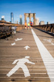 Pathway sign on Brooklyn Bridge with few colorful joggers. In the background royalty free stock image