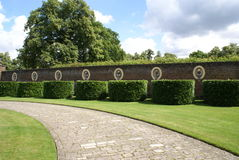 Pathway with statues in alcoves and topiary trees Royalty Free Stock Images