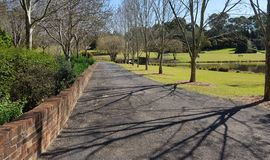 The Pathway. A pathway surrounded by trees, gardens and ponds on a sunny day Royalty Free Stock Image