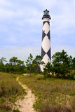 Pathway to Cape Lookout Light. A sandy pathway leads to the historic Cape Lookout Lighthouse, first lit in 1859. The lighthouse, with its distinctive black and Stock Photo