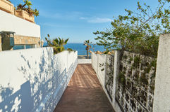 Pathway to the sea in Marbella. With blue sky and palmtrees, white walls Royalty Free Stock Photos