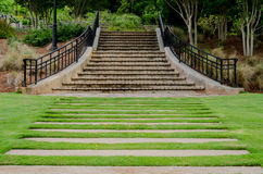 Pathway to Stairs in Garden. Wide stepping stones make a path to concrete and stone stairs in a public garden royalty free stock photos