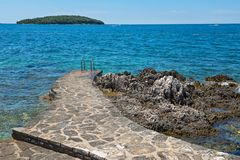 Pathway on the rocky beach in Istria. Pathway on the typical rocky beach in Istria, Croatian coast. Blue transperent sea and sky royalty free stock images