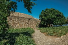 Pathway and wall in a lawn garden with leafy trees. Cobblestone pathway and wall in a lawn garden with leafy trees, on sunny day at the Marvao Castle. An amazing royalty free stock images