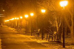 Pathway in winter park with row of lanterns. Stock Image